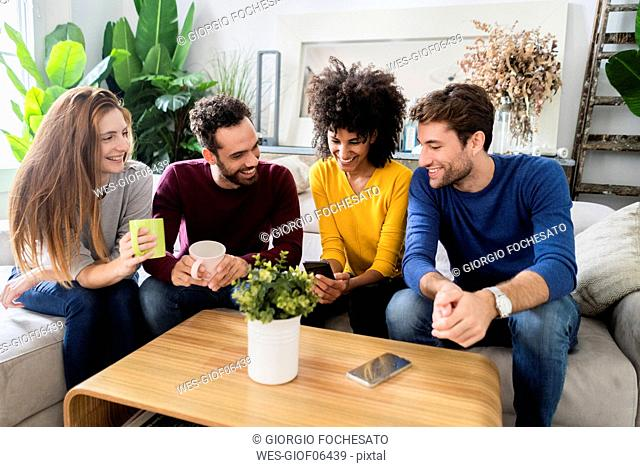 Four happy friends sitting on couch using cell phone