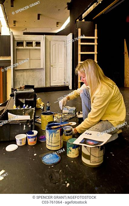 A high school student mixes paint while building the set of a play in her school's theatre  Stagecraft is an elective course at the school