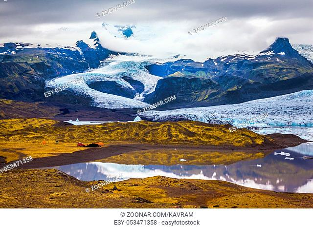 The concept of northern extreme tourism. The largest glacier in Iceland - Vatnajokull in the summer sunset. Glacier provides water Ice Lagoon Jokulsarlon