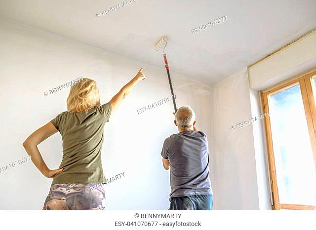 Housewife with painter at work showing the job painting a white ceiling with paint roller in empty room for renovation