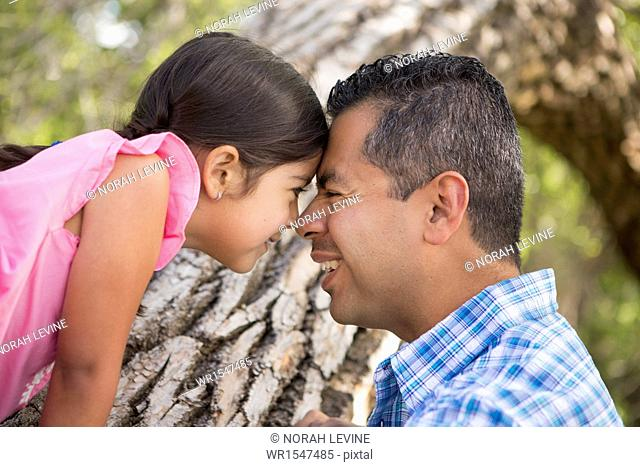 A father and daughter with foreheads pressed together by a tree in the park