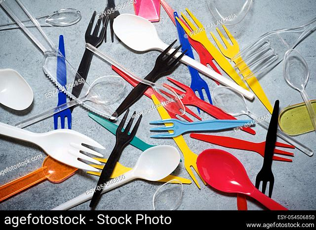 Multicolored plastic cutlery on a stone table