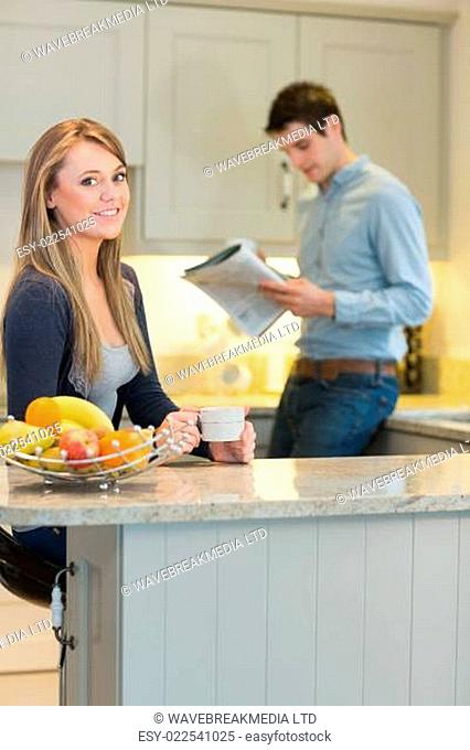 Smiling woman drinking hot drink with man reading newspaper