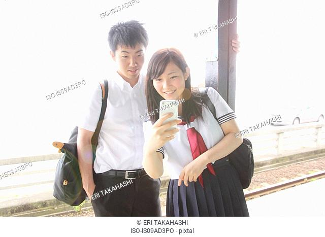 Young couple on railway platform looking at smartphone