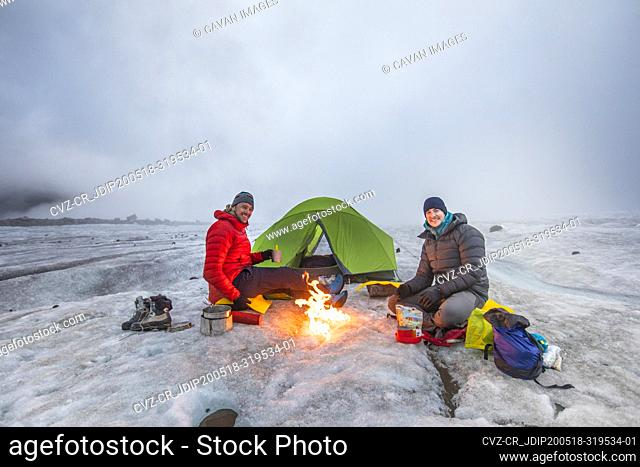 Teo mountaineers enjoys campfire while camping on a glacier