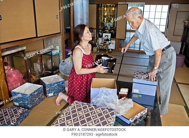 Daughter helps elderly father pack obon decorations in home, Tosu, Saga, Japan