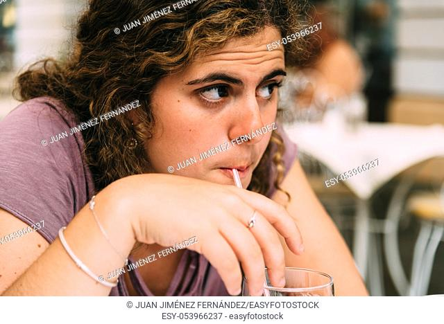 Young woman doubtful while drinking soda. Concept yearning