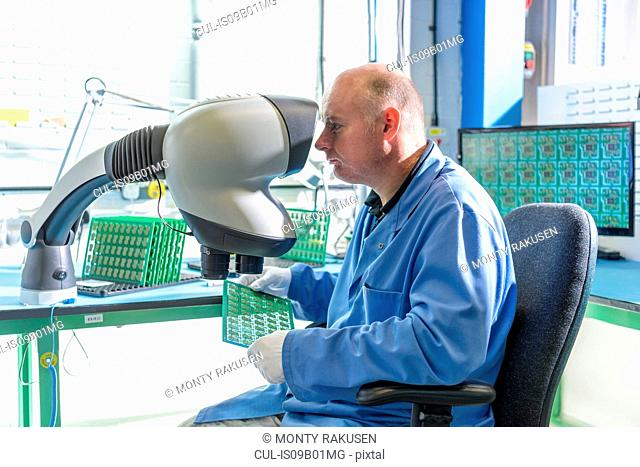 Worker inspecting circuit boards in circuit board assembly factory