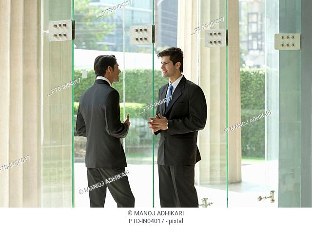 India, Two businessmen talking in office lobby