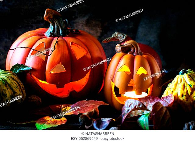 Halloween's pumpkins with autumn leaves on wooden table. See series