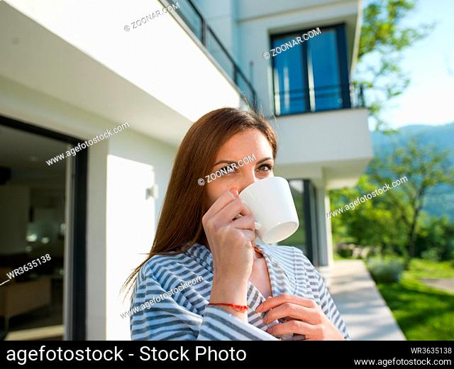 young beautiful woman in a bathrobe enjoying morning coffee in front of her luxury home villa