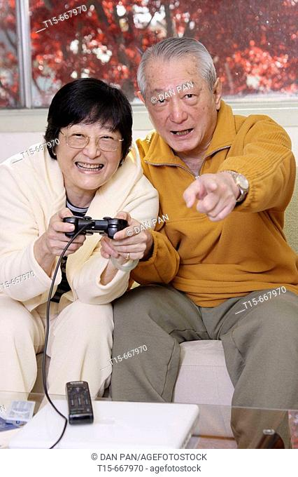 Senior Asian couple having fun playing video playstation games on tv