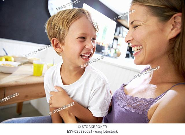 Mother Sitting With Laughing Son At Breakfast Table