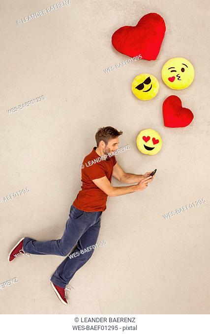 Man chatting on his smart phone, sending emojies