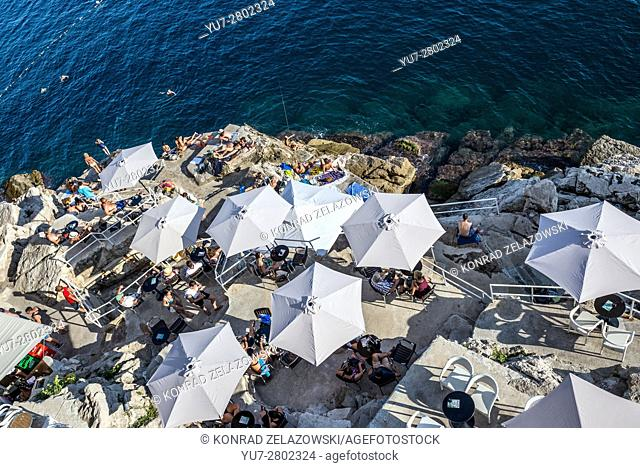 restaurant umbrellas on the rocks under the Old Town Walls of Dubrovnik in Croatia