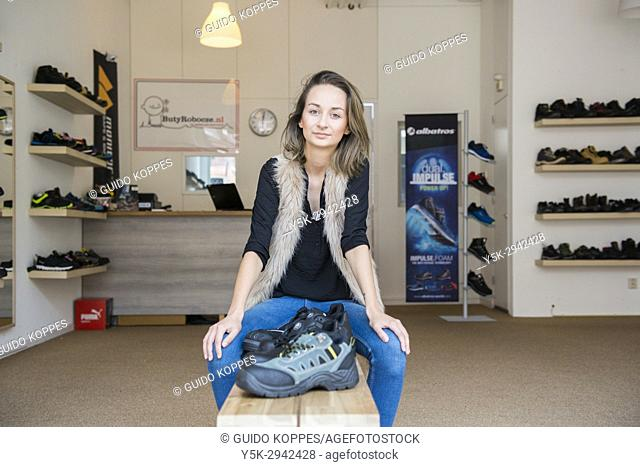 Tilburg, Netherlands. Young adult Polish woman working from a down town safety shoe store, servicing Eastern-European labor immigrants
