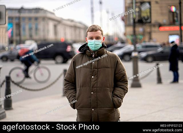 Young man with face mask, commuting in the city, St. Petersburg, Russia