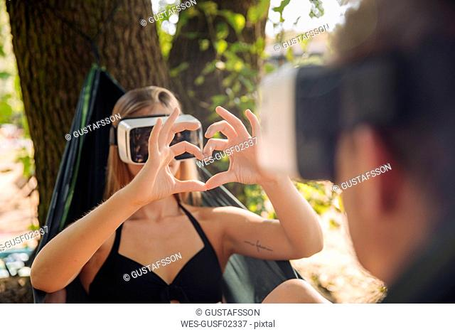 Couple relaxing in hammock by the lake, using VR goggles, woman showing heart shape finger frame