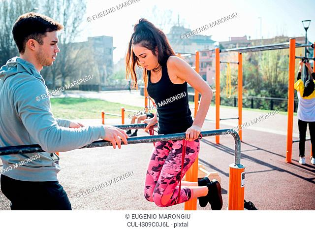 Calisthenics at outdoor gym, trainer watching young woman on parallel bars