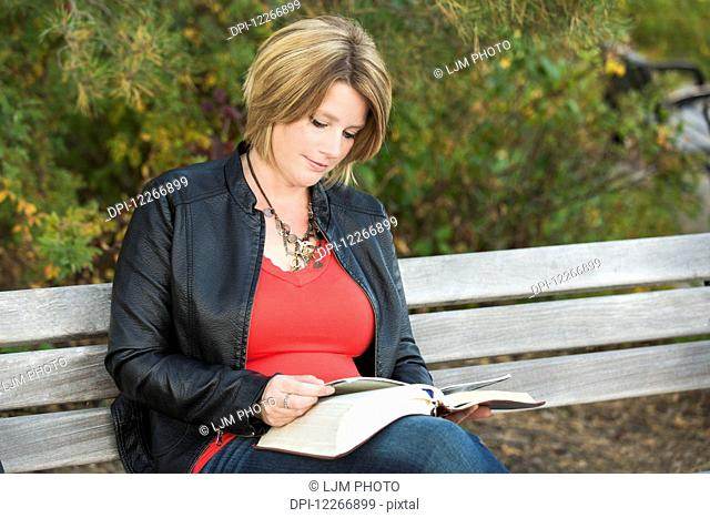 Mature Christian woman studying her Bible in a park; Edmonton, Alberta, Canada