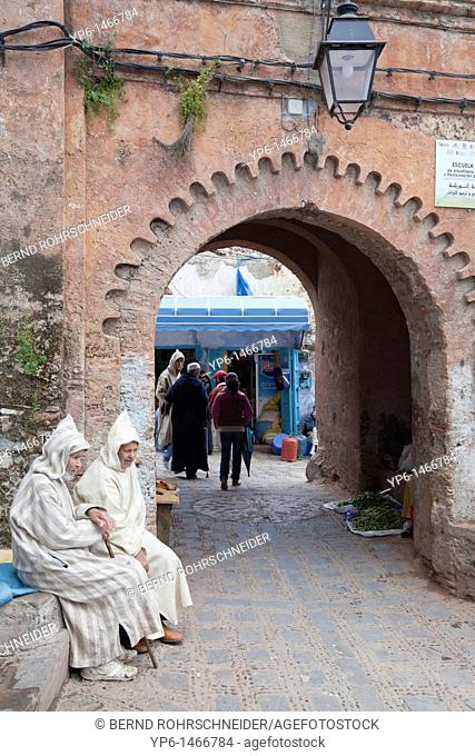 Medina with archway and traditional dressed men, Chefchaouen, Morocco