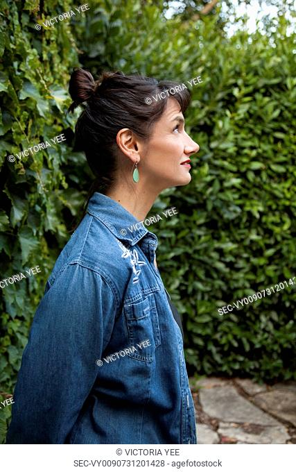Profile of woman against hedge