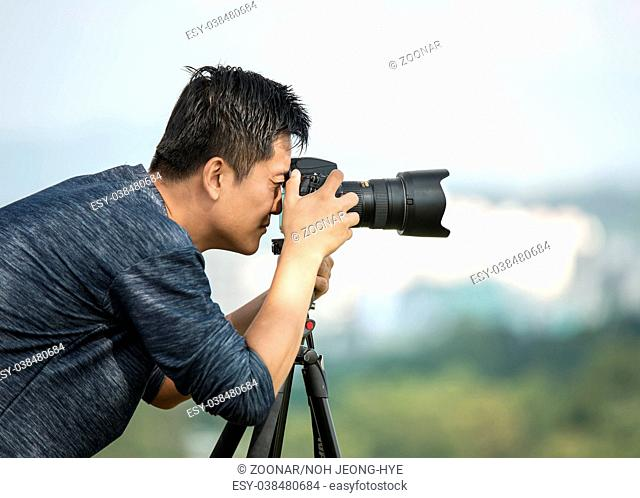 Professional travel on location and nature videographer/photographer (man) photographing nature