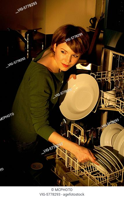 Eine junge Frau nimmt das Geschirr aus dem Geschirrspueler, 2005 - Germany, 21/07/2005