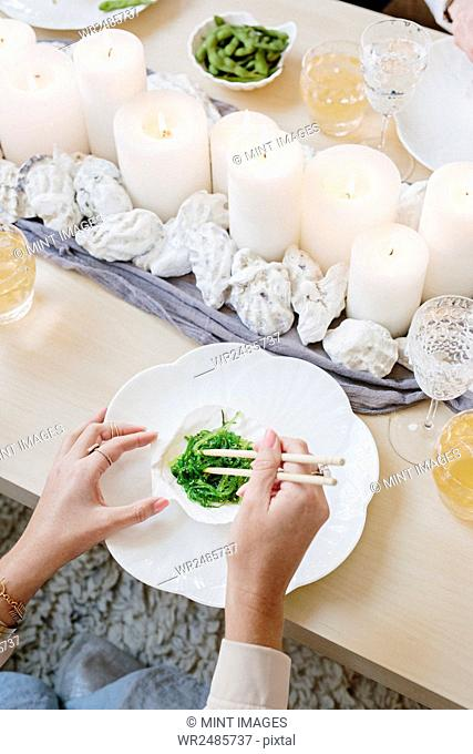 Overhead view of a table with candles and a person using chopsticks to eat green vegetables