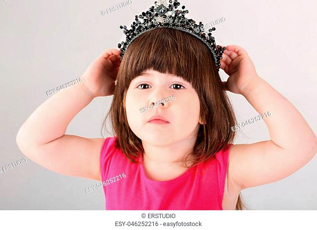 74eac28cc008 portrait of beautiful little brunette girl in pink Princess dress with a  crown on a gray
