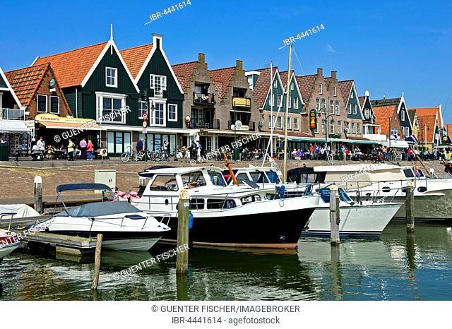 Motorboats at dock, houses along harbor, Volendam, North Holland Province, Holland, The Netherlands