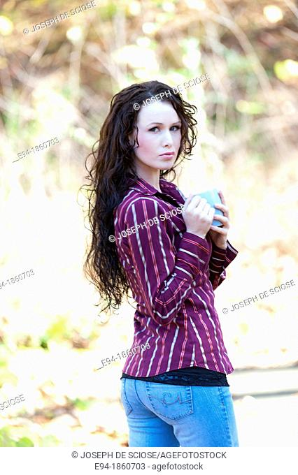 Portrait of 24 year old brunette woman holding a coffee cup in a back yard in the fall