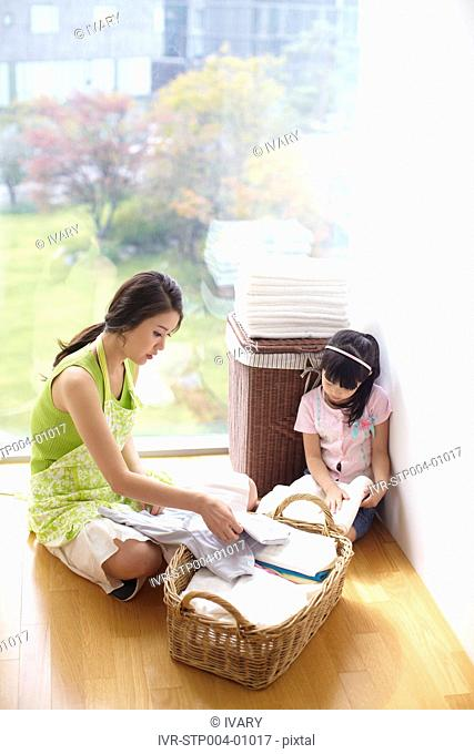 Mother And Daughter Arranging Laundry In Basket