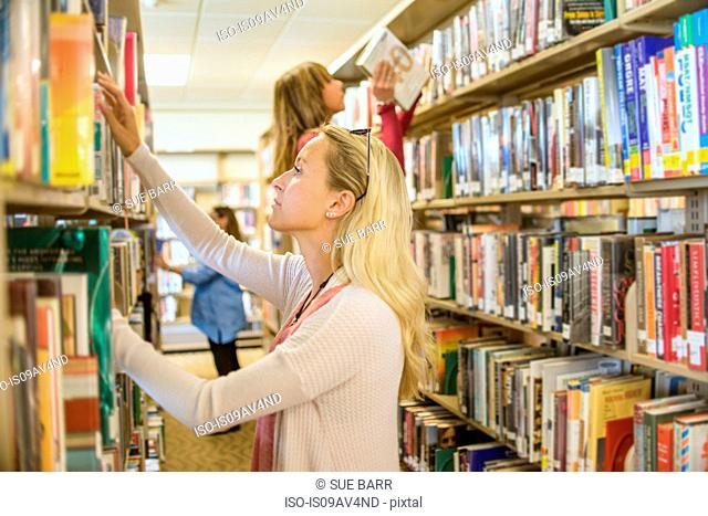 Female customers searching for books in library
