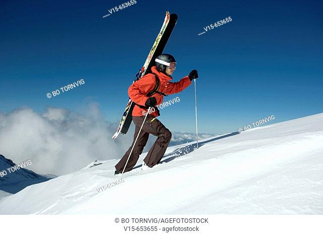 Off-piste skier climbing snow covered mountain with telemark skies