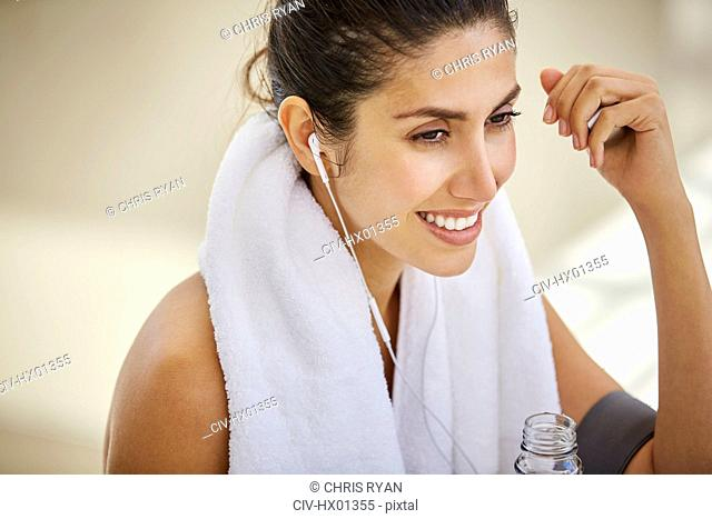 Smiling woman with towel listening to music with headphones post workout