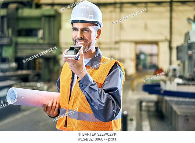 Smiling man holding blueprints and using cell phone in factory