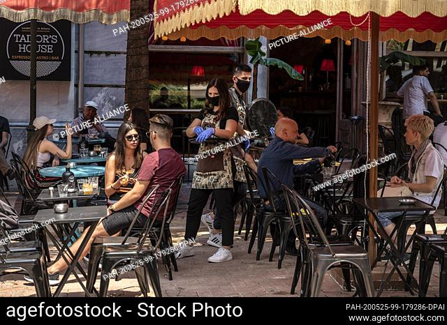 25 May 2020, Greece, Athen: A waitress with a face mask and disposable gloves takes an order in a cafe. Greece relaxes measures imposed because of the Corona...