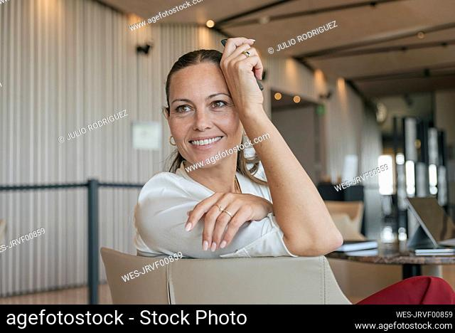 Happy female entrepreneur looking away while sitting on chair in lobby