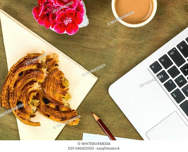Pain Au Raisan Spiral French Pastry and a Cup of Tea At A Computer Workstation