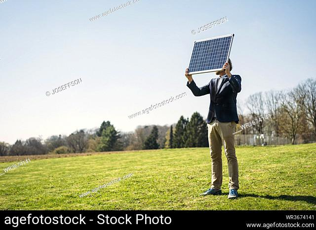 Male professional holding solar panel while standing on grass at park against clear sky during sunny day