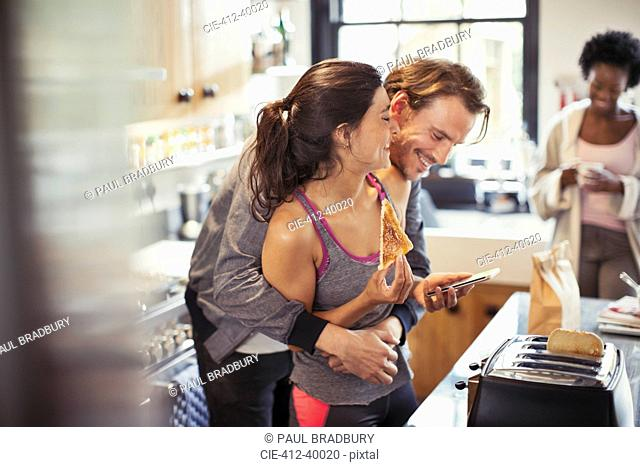 Playful couple hugging, texting with smart phone and eating toast
