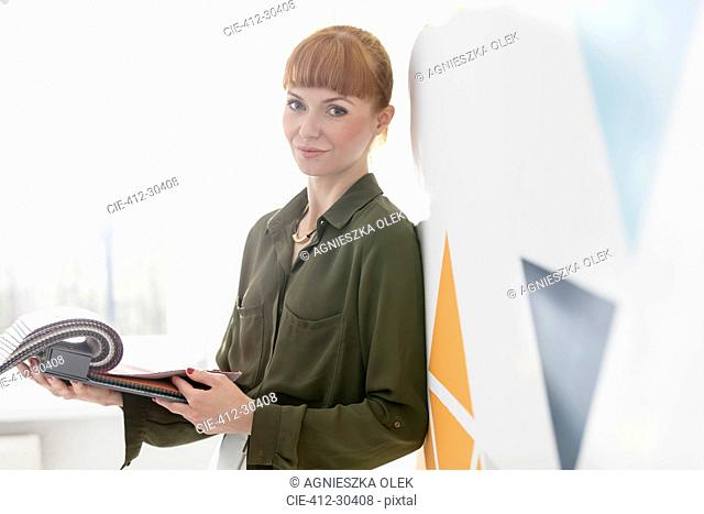 Portrait confident interior designer looking at fabric swatches