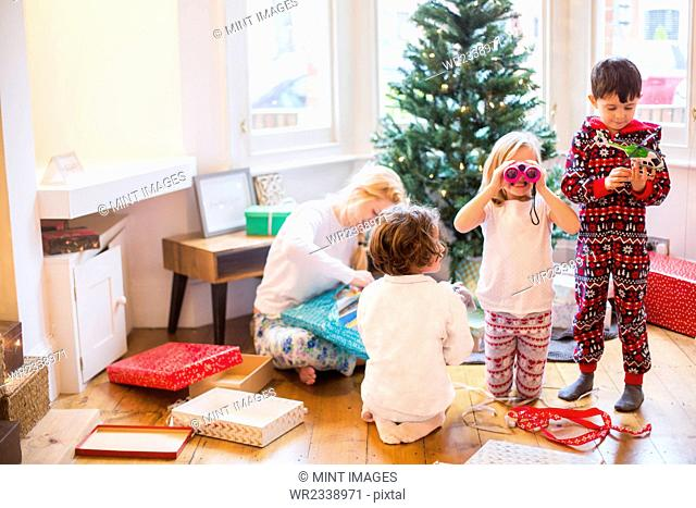 A mother and three children on Christmas morning opening presents
