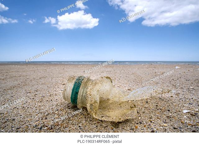 Old partly broken down plastic bottle, non-biodegradable waste washed ashore on sandy beach along the North Sea coast