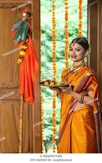 Maharashtrian woman in traditional dress celebrating gudi padwa festival holding a pooja plate looking at camera
