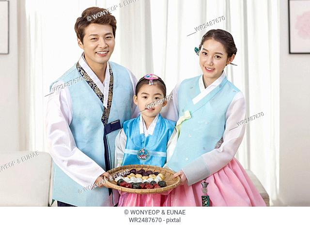Smiling daughter and her parents in traditional Korean clothes posing with rice cake