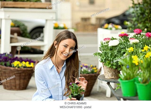 Young woman buying potted flowers