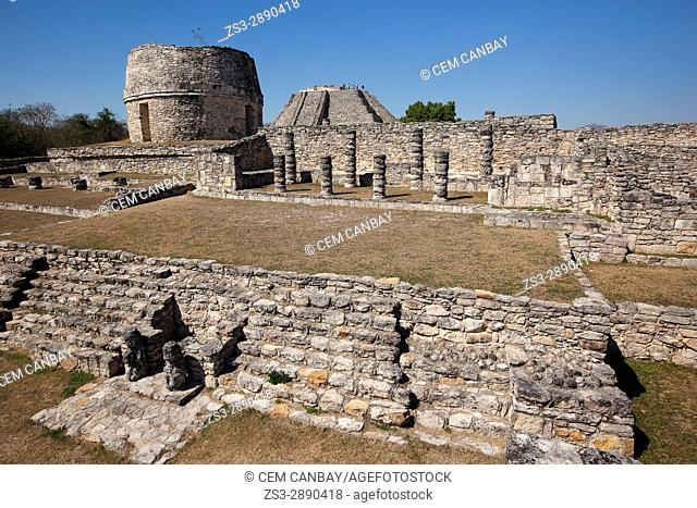 View to the Templo Redondo-Round Temple and visitors standing at the top of the Castle of Kukulcan-Castillo de Kukulcan in Mayapan Archeological site, Merida