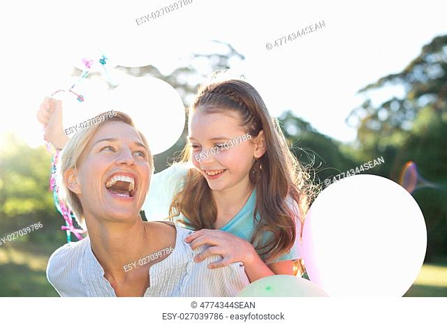 Happy mother playing with her daughter on a sunny day